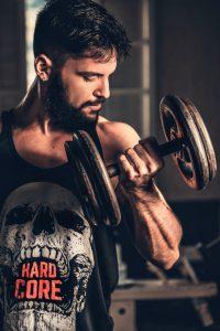 человек, делающий упражнения с гантелями