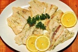 Рыба с ломтиками лимона на тарелке
