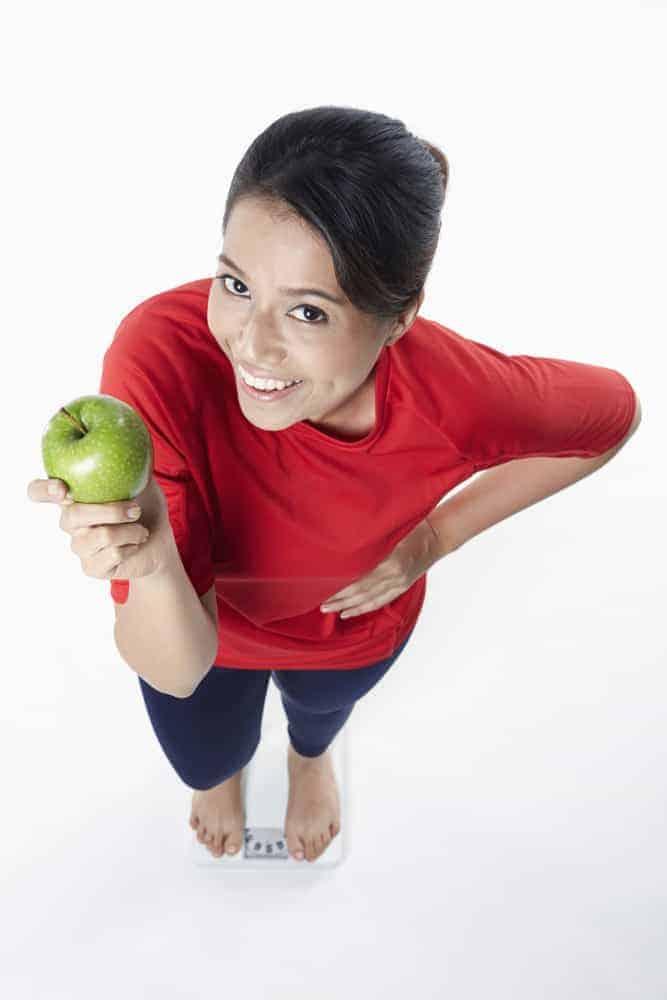 женщина держит яблоко в руке