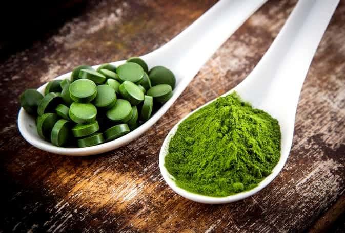 Ложка высушенных водорослей и таблетки водорослей