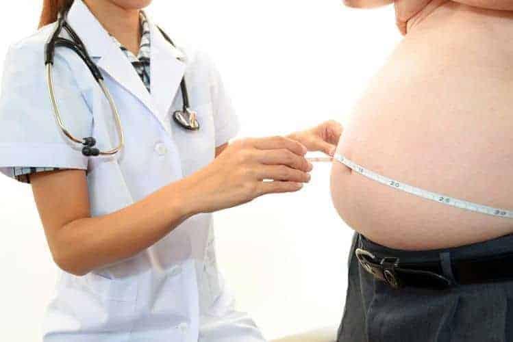 врач измеряет окружность брюшной полости у страдающего ожирением человека