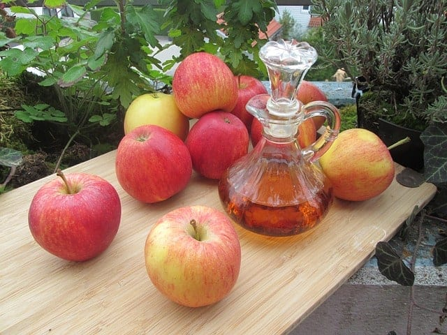 Свежие яблоки и бутылка яблочного уксуса на столе