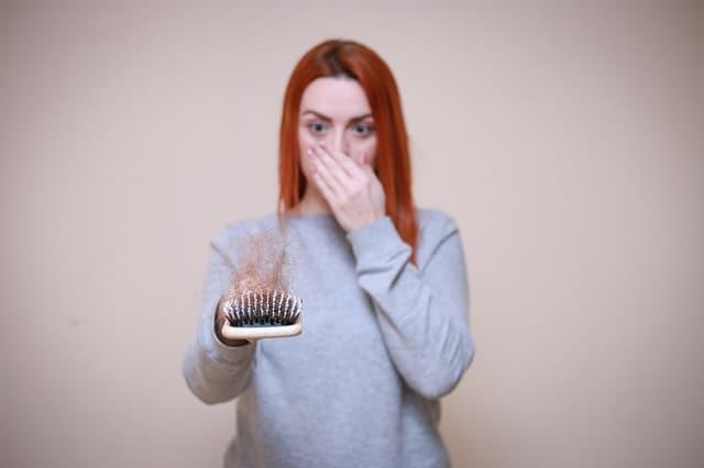 женщина смотрит на расческу, полную волос.