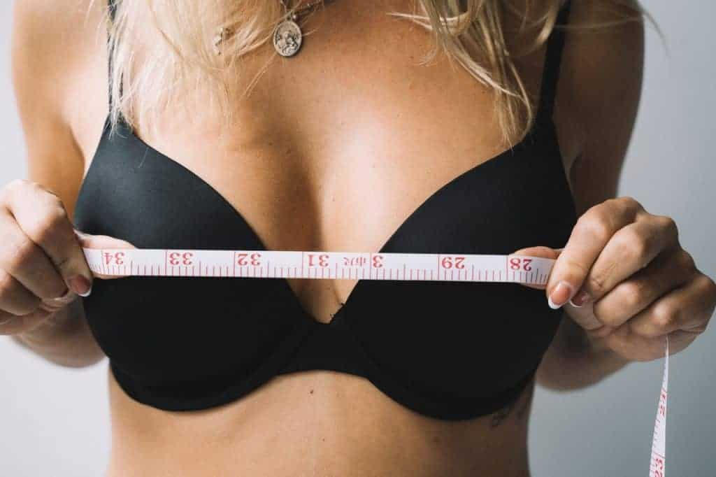 женщина измеряет грудь сантиметром
