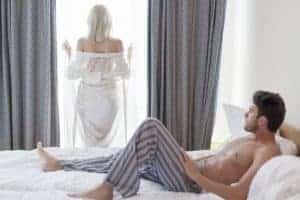 мужчина лежит на кровати, женщина стоит у окна.