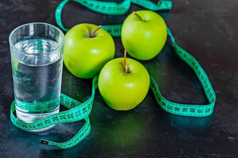 Стакан воды, зеленые яблоки и измерительная лента.