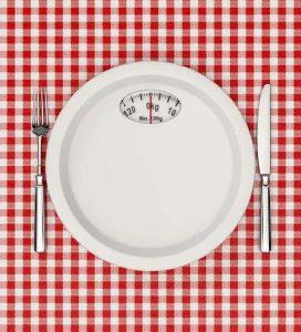 Градуированная тарелка с весом и столовые приборы на столе.