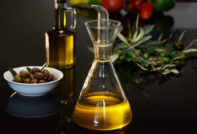 бутылка оливкового масла и зеленые оливки
