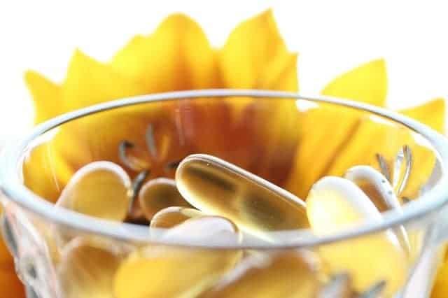 Таблетки в стакане, желтый цветок на заднем плане.