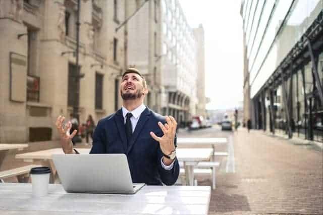 нервный человек, работающий за ноутбуком.