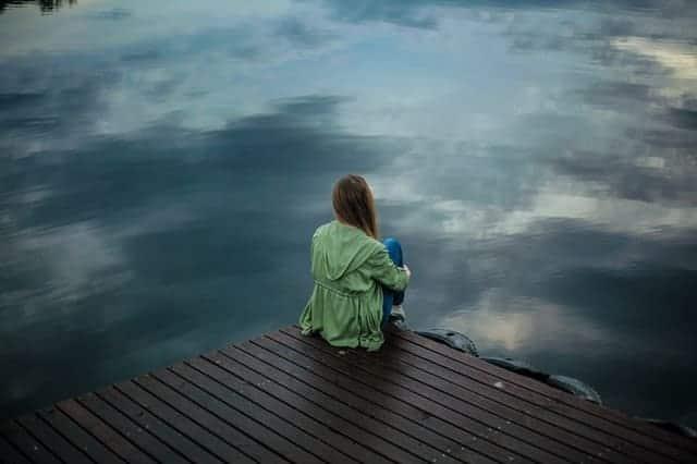 женщина сидит на краю пирса и смотрит в воду.