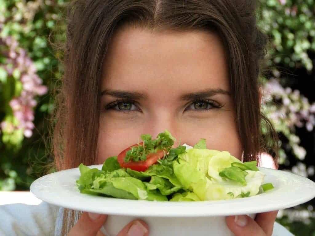 женщина держит тарелку с салатом
