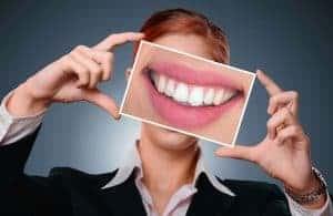 женщина показывает нам фото своих зубов