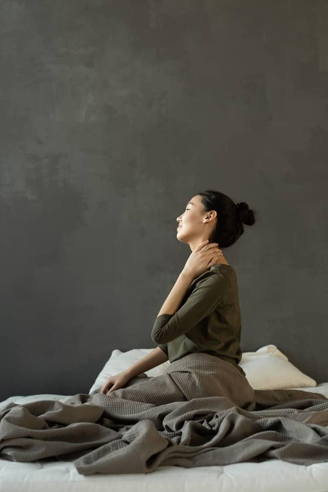 женщина сидит на кровати и держит шею, болит спина.