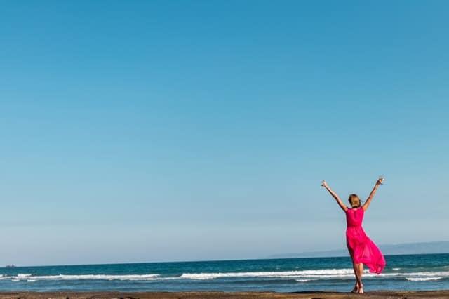 женщина в красном платье, стоящая на берегу