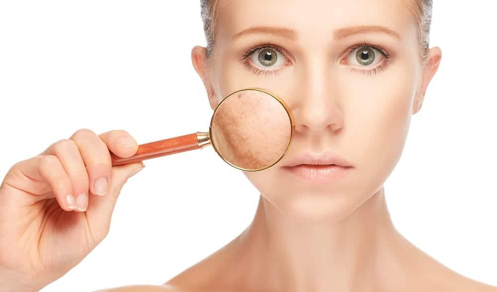 Женщина рассматривает свой цвет лица через увеличительное стекло