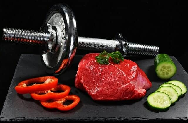 Гантели, кусок мяса и овощи