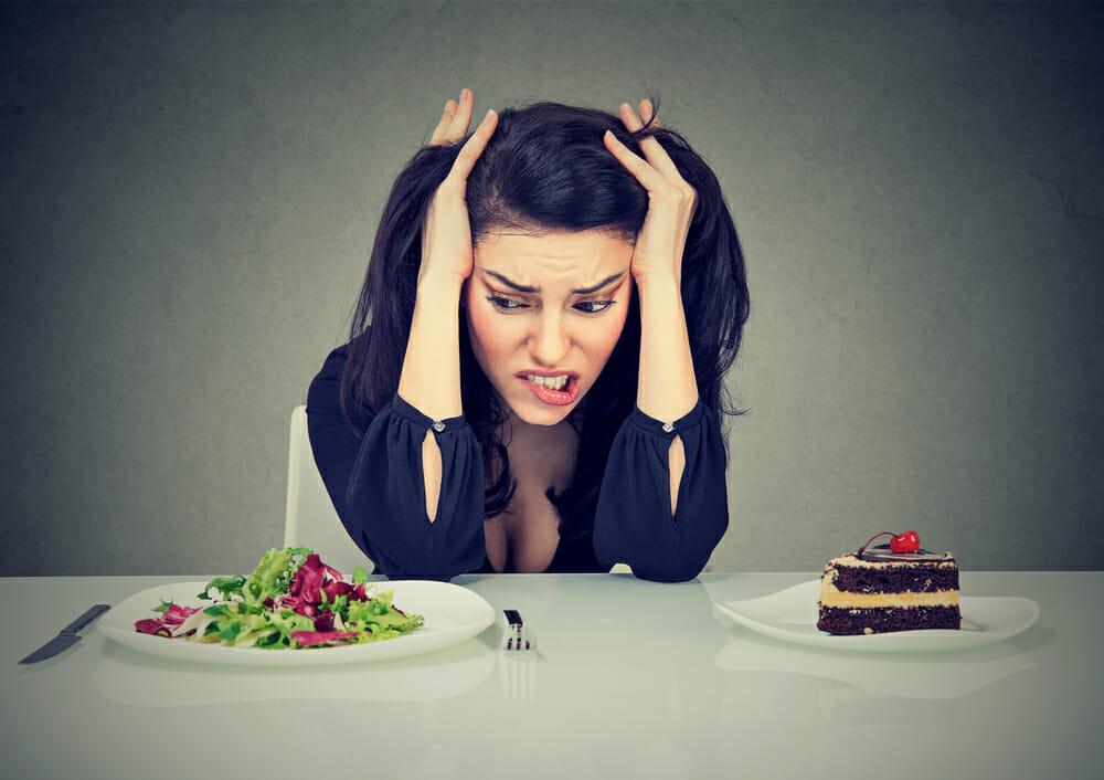 женщина сидит за столом с тарелкой торта и тарелкой салата