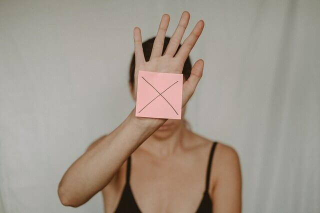 грустная женщина держит перед собой картонную коробку с буквой